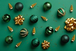 Gold Christmas tree decoration and baubles on green background. Flat lay, top view. Merry Christmas card