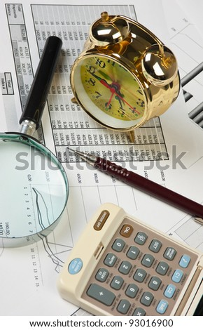 gold clock and office supplies on the table