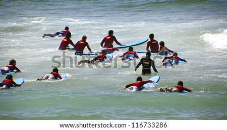 GOLD COAST, AUSTRALIA - SEPT 09 2012 : Unidentified surf students in  Surfers Paradise taking the first lessons to become good surfers.  on Sept, 09, 2012 in Gold Coast Australia . - stock photo