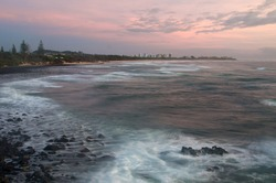 Gold Coast in the distance at sunset with the beach and rocks at Fingal Heads in the foreground