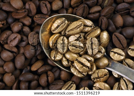 Gold coffee beans on a pile of coffee beans. The concept of luxury is extraordinary. Coffee beans in a spoon. Golden coffee beans texture background