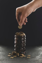 Gold coin in hand and piggy bank on black background, growth in savings. Economic crisis and saving money. Donation to charity fund.