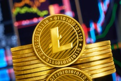 Gold coin litecoin stacked on a bright background of business graphics close-up. Crypto-currency LTC. Anonymous. Virtual currency