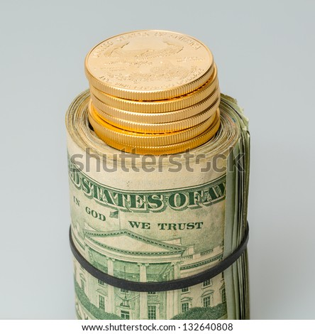 Gold coins standing on roll of many $20 dollar bills and notes secured by elastic band on white table