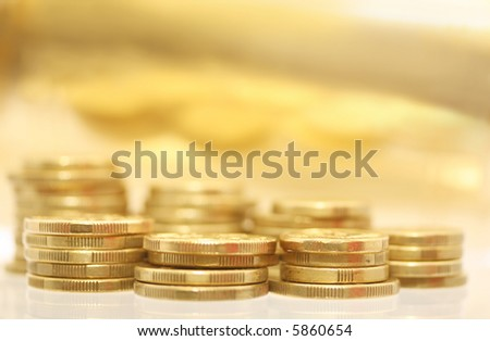 Gold coins, with golden reflection in the background.  Very shallow DOF.