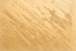 Gold colored paint with decorative texture. Decorative plaster and paint on the wall with brushed gold color. texture formed by golden brush strokes.