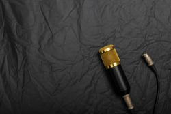 Gold condenser microphone with signal cable Place on a black cloth with uneven wrinkles.