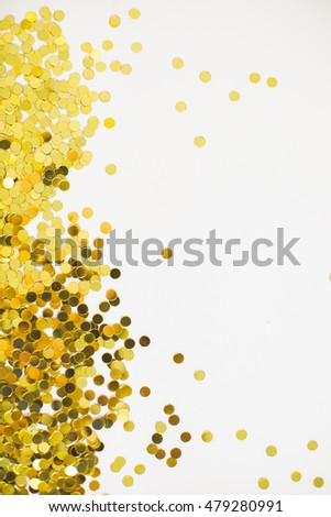 gold confetti scattered from side of frame fading to white with copy space vertical