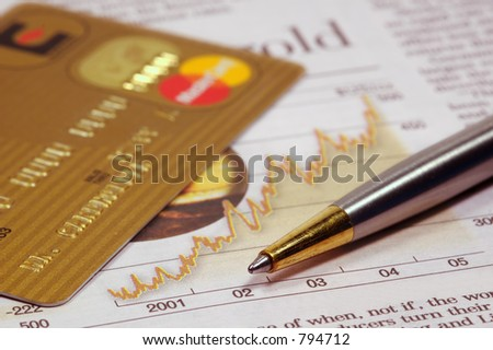 Gold credit card, financial newspaper and a pen