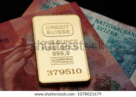 Gold credit suisse swiss bank golden bar, one ounce fine 999,9 fine gold bullion, lying on red 20 swiss franc bank note, detail close up
