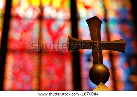 Gold cross and colorful stained glass window