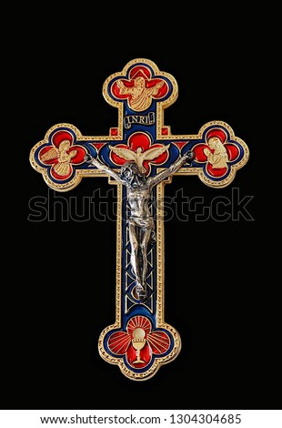 Gold crucifix with silver body of Jesus Christ and images of Father Holy Spirit angel and prayer isolated on black background. Concept of three persons yet one God