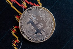 Gold crypto coin on the chart. Close-up photo of bitcoin. High quality photo