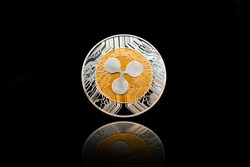 Gold cryptocurrency coin - Ripple coin with isolated on a black background.