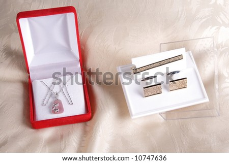 Gold cuffs and tie pin and necklace in jewelry boxes