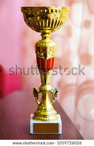 Gold Cup on wooden table #1059726026