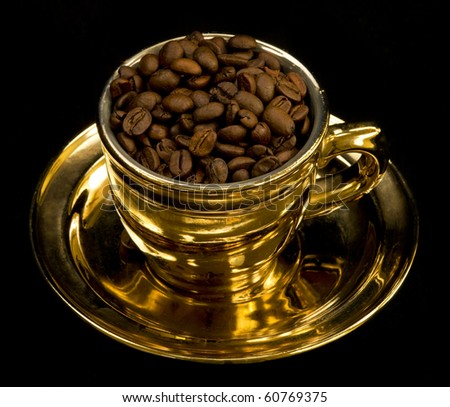 Gold cup with coffee beans on black background