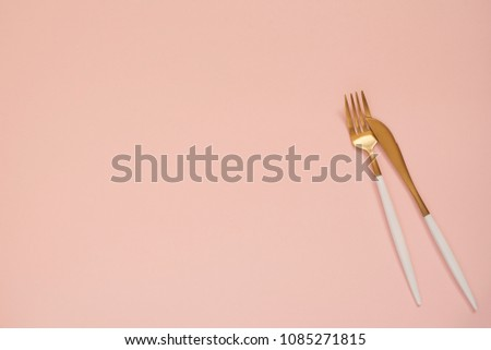 Gold cutlery. Golden spoon set, golden knife and fork on the table. Luxury spoon set top of view. Pastel punchy pink background
