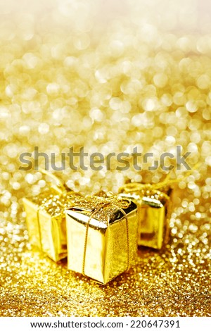 Gold decorative boxes with holiday gifts on abstract gold background