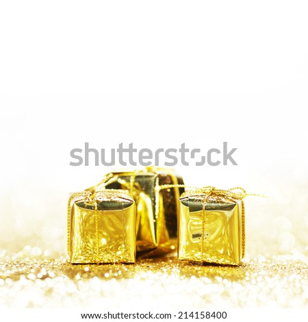 Gold decorative boxes with holiday gifts on gold glitters isolated on white