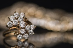 Gold diamond jewelry on a black background. Jewelry is reflected on the mirror surface. Rings and bracelets.