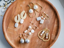 Gold earrings. Women's jewelry. Vintage decoration background. Beautiful golden tones brooches, bracelets, necklaces and earrings on a wooden tray. Flat lay, top view