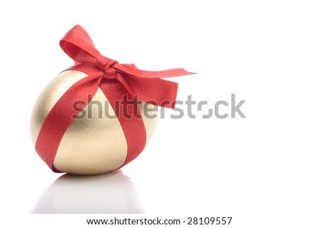 Gold egg with red ribbon over white background