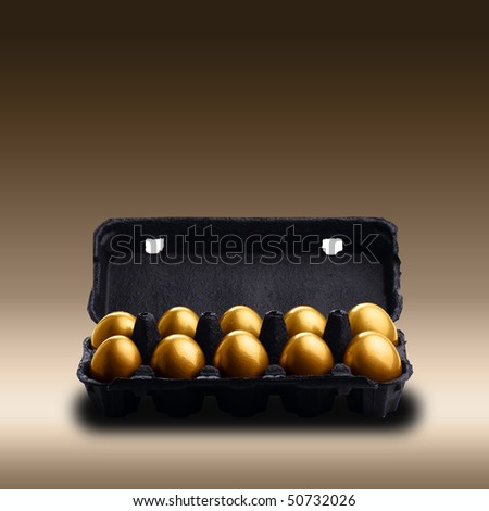 Gold eggs in a black carton on brown background