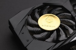 Gold Ethereum coin lies on a black video card, a fan. Crypto currency, ETH. Bitcoin mining concept. Macro