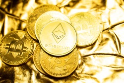 Gold ethereum coins on a golden background. Trading on the cryptocurrency exchange. Cryptocurrency Stock Market Concept. Virtual money concept. Mining or blockchain technology. Business concept.