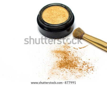 Gold eyeshadow and applicator brush