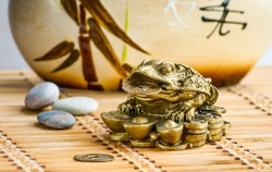 Gold feng-shui frog statuette on a bamboo mat