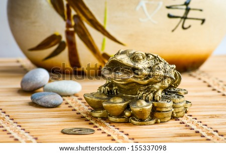 Gold feng-shui frog statuette on a bamboo mat #155337098