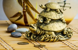 Gold feng-shui turtles statuette on a bamboo mat