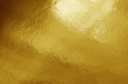 Gold foil background with highlights and uneven texture