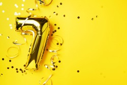 Gold foil balloon number and digit seven 7. Birthday greeting card. Anniversary celebration event. Banner. Copy space. Stylish golden numeral, bright shiny glitter, yellow background. Numerical digit.
