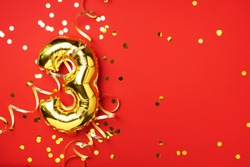 Gold foil balloon number and digit three 3. Birthday greeting card. Anniversary celebration event. Banner. Copy space. Stylish golden numeral, bright shiny glitter, red background. Numerical digit