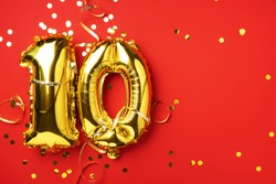 Gold foil balloon number, digit ten. Birthday greeting card with inscription 10. Anniversary celebration event. Banner. Golden numeral, red background. Numerical digit, bright shiny glitter.