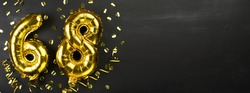 gold foil balloon number sixty eight. Birthday or anniversary card with the inscription 68. Black concrete background. Anniversary celebration. Banner. copy space