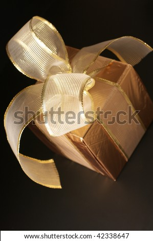 Gold foil gift with gold translucent bow on black background.