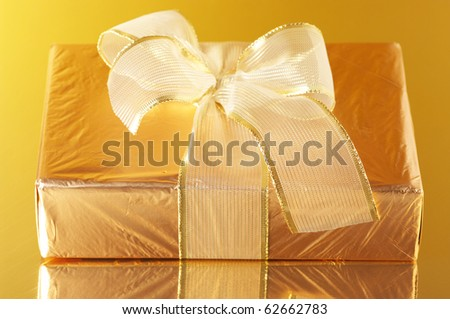 Gold foil gift with golden bow on golden background with reflection.