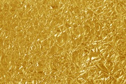 Gold foil leaf shiny texture, abstract yellow wrapping paper for background and design art work.