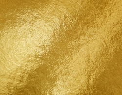 Gold foil texture background with highlights and uneven surface