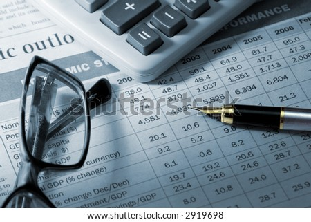 gold fountain pen, eyeglasses and calculator on the table of financial statement
