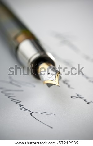 Gold fountain pen on hand written letter with selective focus on tip of pen nib.