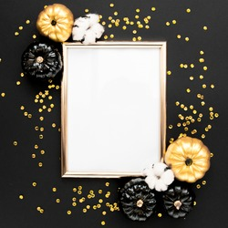 Gold frame decorated with black and gold Halloween pumpkin and tinsel with copy space for text. isolated on black background. Flat lay, top view.