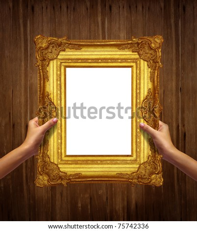 gold frame in woman hand isolated on old wood background