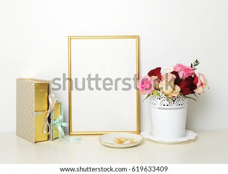 Gold frame mock-up, and white wall with gold apple, and roses. Place work