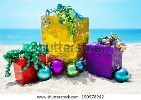 Gold gift bag and two gift boxes with Christmas balls on sandy beach in sunny day- holiday concept