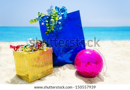Gold gift box and blue gift bag with Christmas ball on sandy beach in sunny day- holiday concept